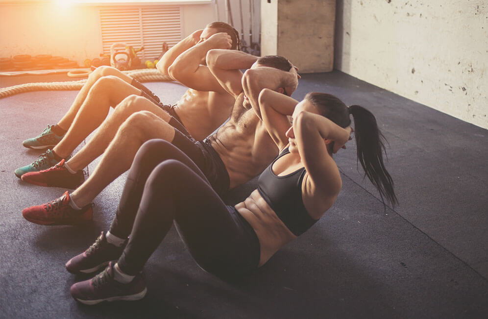 group of adults doing sit up exercises